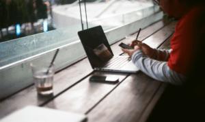 homme devant un notebook dans un café