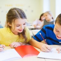 écoliers écrivant sur des cahiers
